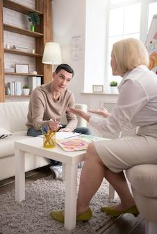 Nouvelle méthode psychologique. attrayant bel homme consultant avec un psychologue tout en dessinant