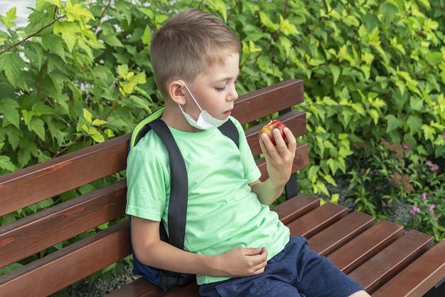 Nouvelle normalité, retour à l'école. écolier portant un masque médical et un sac à dos prendre un déjeuner sur un banc pendant la récréation