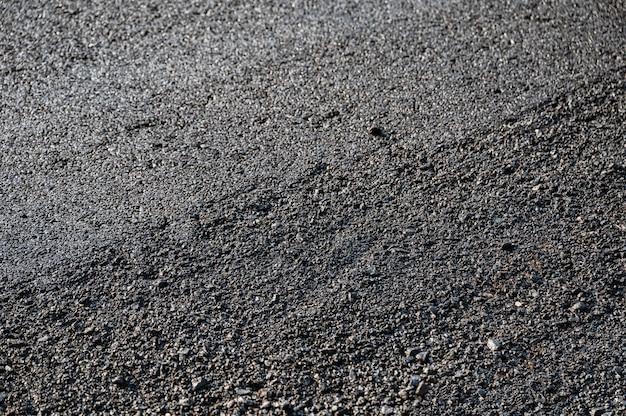 Nouvelle route de texture goudronnée d'asphalte de réparation sur la route endommagée dans le chantier de construction
