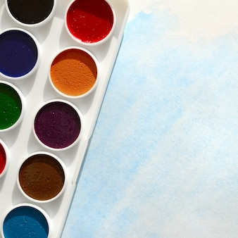 Une nouvelle série d'aquarelles repose sur une feuille de papier, qui montre un dessin abstrait à l'aquarelle