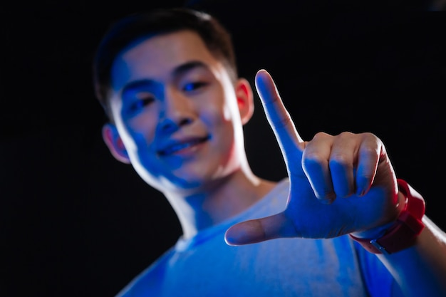 Nouvelle technologie. mise au point sélective d'une main de jeune homme touchant l'écran numérique