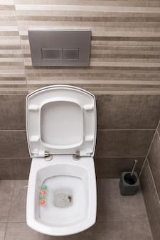 Nouvelle toilette en céramique blanche sur fond de carrelage gris. l'intérieur des toilettes. style moderne.