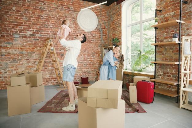 Nouvelle vie. la famille adulte a déménagé dans une nouvelle maison ou un nouvel appartement. les conjoints et les enfants ont l'air heureux et confiants. déménagement, relations, nouveau concept de vie. déballer les cartons avec leurs affaires, jouer ensemble.