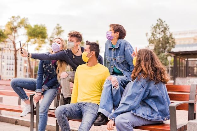 Nouvelle vie normale du virus corona avec un groupe multiracial de jeunes étudiants prenant un selfie avec un masque facial