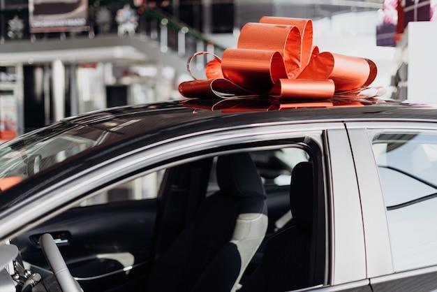 La nouvelle voiture est enveloppée d'un arc rouge. beau concept de cadeau