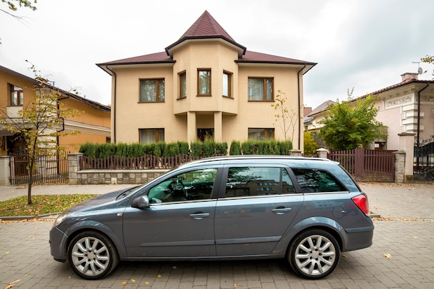 Nouvelle voiture grise chère garée dans un parking pavé en face d'un grand chalet de deux étages.