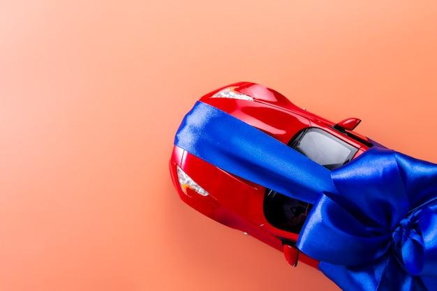 Nouvelle voiture rouge avec un arc bleu en cadeau sur du corail