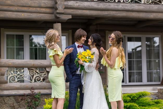 Nouvellement marié avec des demoiselles d'honneur lors de la cérémonie de mariage posant à la villa
