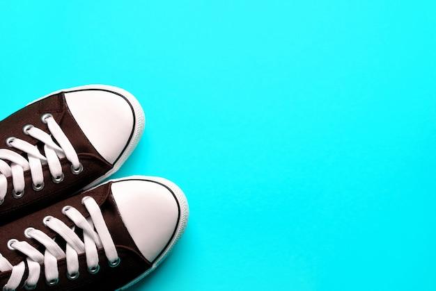 Nouvelles baskets athlétiques bleues propres avec des lacets blancs, sur un fond bleu pastel.