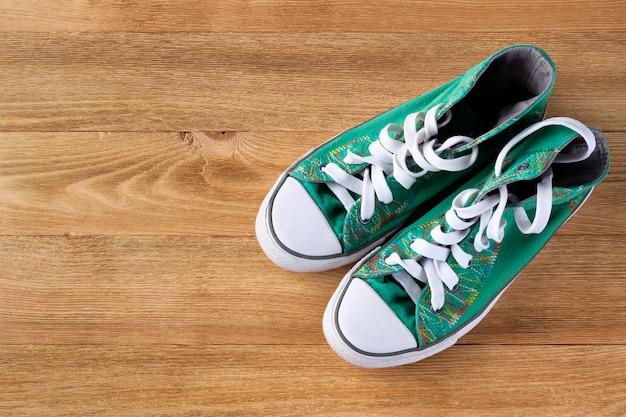 Nouvelles baskets athlétiques vertes propres avec des lacets sur un fond en bois.