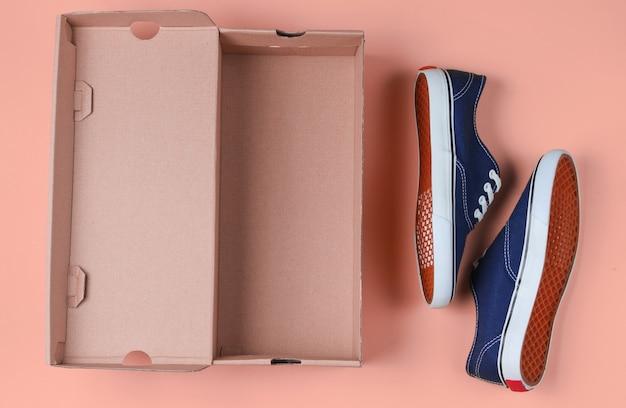 Nouvelles baskets à la mode et boîte en carton vide sur rose