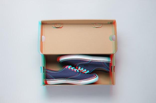 Nouvelles baskets à la mode dans une boîte en carton sur gris