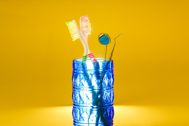 Nouvelles brosses à dents en plastique à l'intérieur d'un verre, isolé sur orange vif