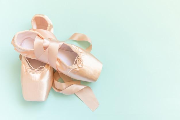 Nouvelles chaussures de ballet beige pastel avec ruban de satin isolé sur fond bleu
