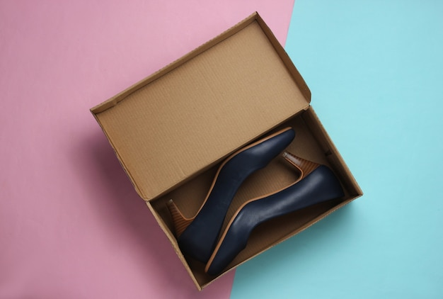 Nouvelles chaussures en cuir avec une boîte en carton sur un fond pastel bluepink cadeau pour femme