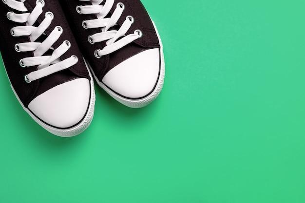 Nouvelles chaussures de sport bleues propres avec des lacets blancs, sur un fond vert pastel.