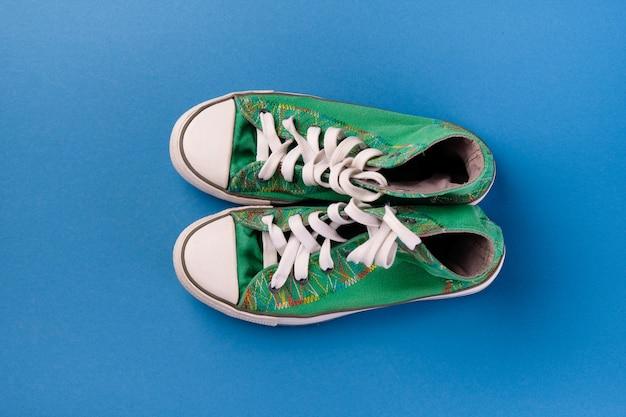 Nouvelles chaussures de sport vertes propres avec des lacets sur un fond bleu vif.