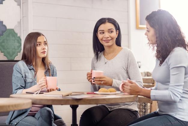 Des nouvelles choquantes. élégantes jeunes trois amis appréciant le café en visitant le café et en discutant
