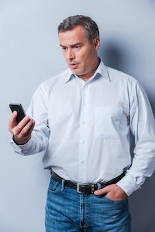Nouvelles choquantes. homme mûr surpris en chemise tenant un téléphone portable et le regardant en se tenant debout sur fond gris