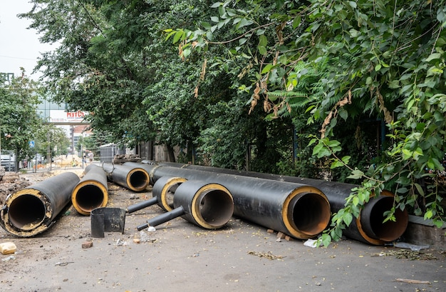 Nouvelles conduites d'eau noire isolées se trouvant à l'extérieur en journée d'été près des arbres verts