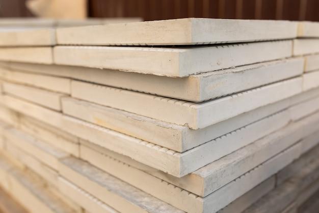 De nouvelles dalles de pavage emballées dans des matériaux de construction en pile sur un chantier de construction