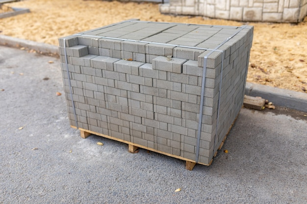 Nouvelles dalles de pavage emballées en pile sur une palette en bois avant la pose. matériaux de construction sur le chantier