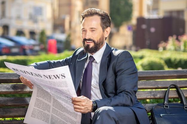 Nouvelles financières. homme d'affaires souriant professionnel reposant sur le banc en lisant un journal