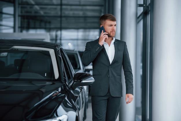 De nouvelles offres arrivent. homme d'affaires barbu élégant et moderne dans le salon automobile