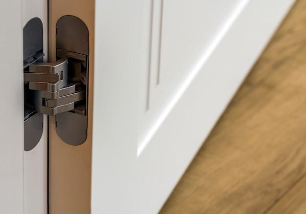 De nouvelles portes métalliques modernes s'articulent sur des portes en bois blanc
