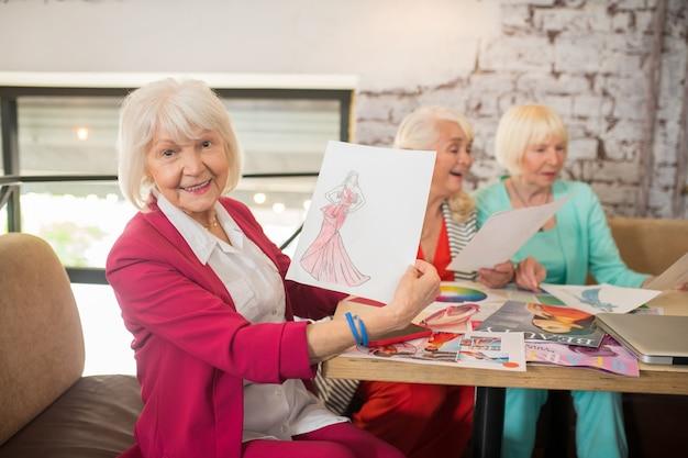 De nouvelles robes. trois dames âgées bien habillées discutant d'une nouvelle collection de robes