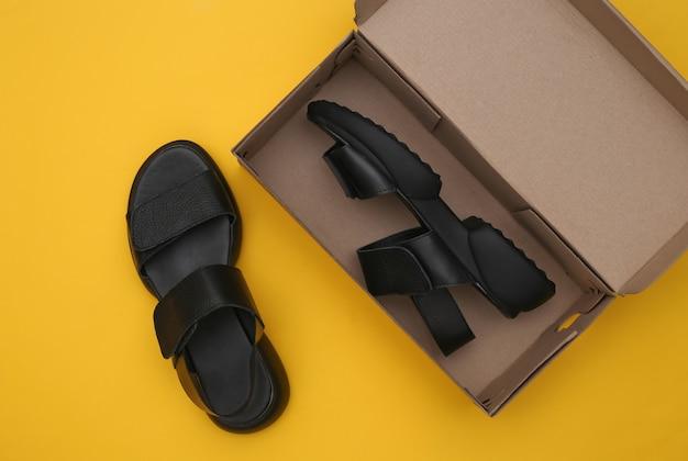 Nouvelles sandales en cuir dans une boîte d'emballage sur fond jaune. vue de dessus