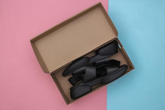 Nouvelles sandales en cuir dans une boîte d'emballage sur fond pastel bleu-rose. vue de dessus