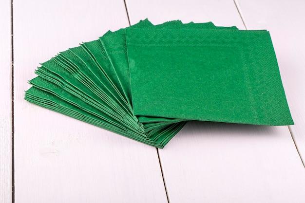 Nouvelles serviettes vertes sur une table à dîner en bois blanc