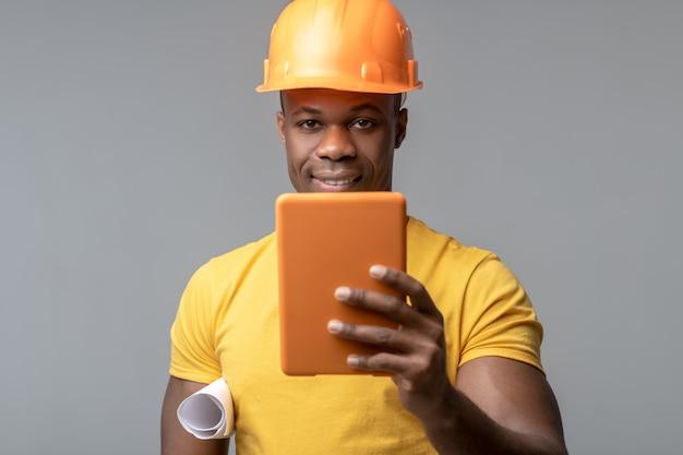 Nouvelles technologies. séduisante jeune afro-américaine souriante en casque de construction orange avec tablette à la main sur fond clair