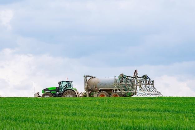 Nove hrady, république tchèque - 23 avril 2019 : le pulvérisateur travaille sur un champ vert. traitement du blé avec un herbicide.