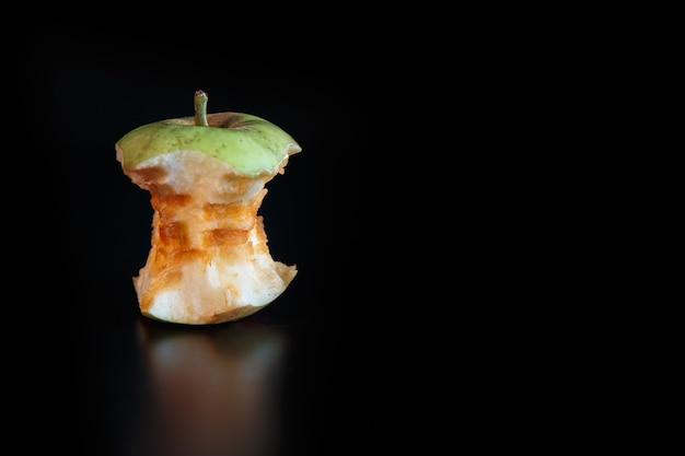 Noyau de pomme sur fond noir avec réflexion. concept d'écologie et de recyclage des déchets.