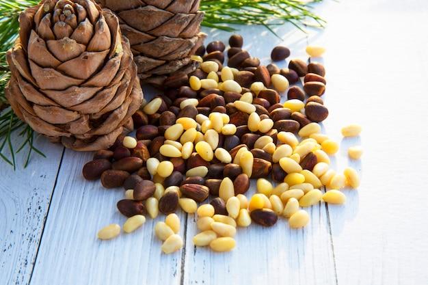 Noyaux pelés de noix de cèdre dans une cuillère, deux pommes de pin, branches vertes et noix dans la coquille contre une planche de bois foncé