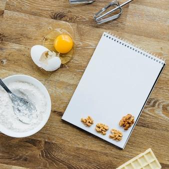 Noyer; bloc-notes en spirale; farine; chocolat et fouet sur une surface en bois