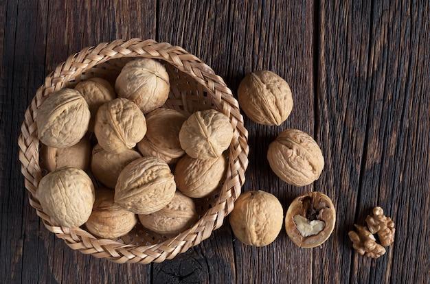 Noyer dans un bol et noyaux de noix sur table en bois foncé, vue du dessus