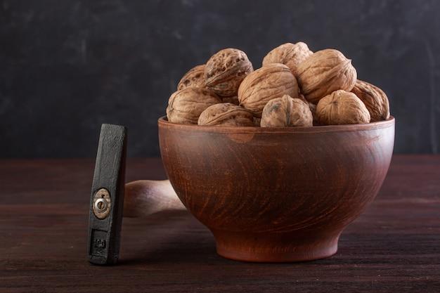 Noyer en poterie et marteau sur une table en bois