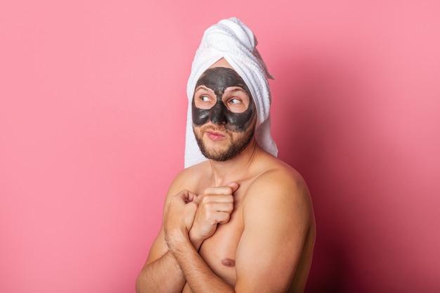 Nu jeune homme appliquant un masque hydratant sur fond rose