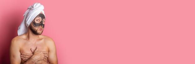 Nu jeune homme couvre ses seins, avec un masque cosmétique sur fond rose