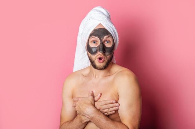 Nu jeune homme avec un masque cosmétique sur son visage, cachant sa poitrine avec ses mains sur un fond rose