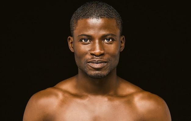 Nu souriant homme africain posant sur fond noir