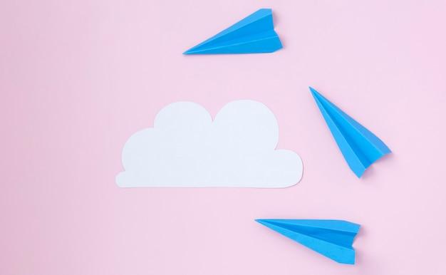 Nuage blanc de papier et d'avions en papier sur fond rose