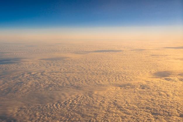 Nuage doré sur le ciel bleu côté extérieur au-dessus de la vue depuis les fenêtres latérales de l'avion au lever du soleil,