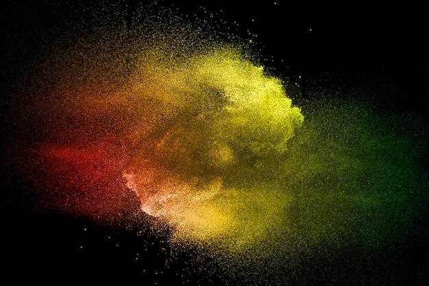 Nuage d'éclaboussure de poussière colorée sur fond sombre. lancé des particules colorées sur le fond.