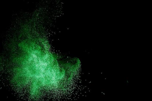 Nuage d'explosion de poudre de couleur verte sur fond noir. éclaboussures de poussière verte.