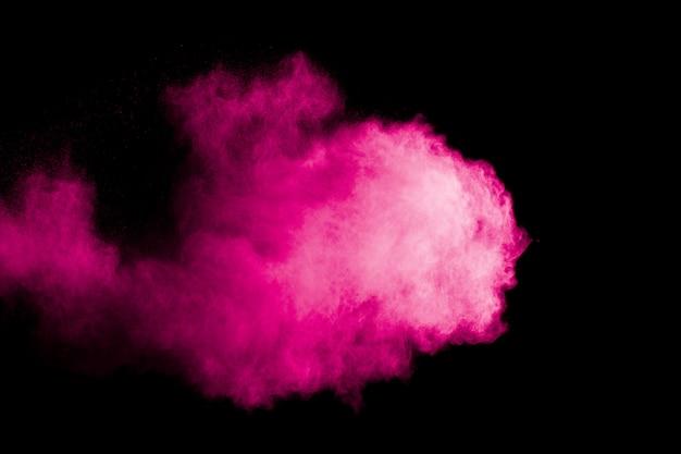 Nuage d'explosion de poudre rose sur fond noir.