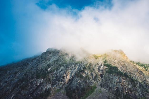 Nuage géant au-dessus de la crête rocheuse avec des arbres au soleil.